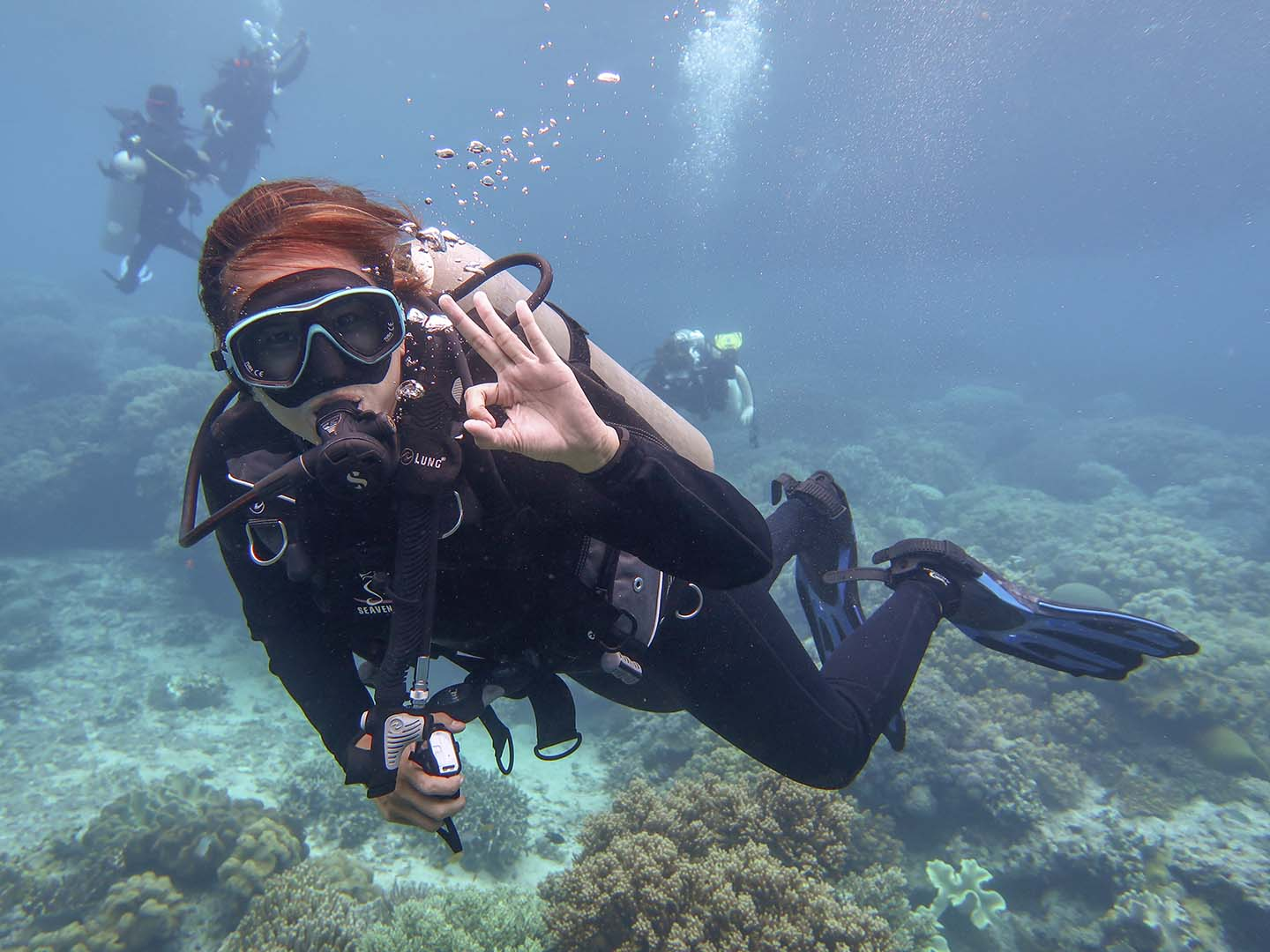 Female scuba diver with okay hand-signal while diving in Apo Island